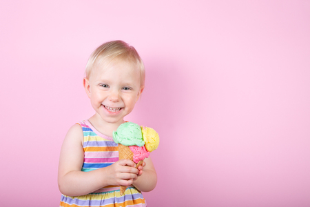 Pretty girl eating ice cream in front of pink background