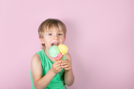 Happy boy eating ice cream in front of pink background