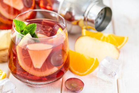 Sangria and ingredients in glasses on wood background