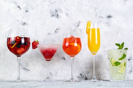 Selection of refreshing summer drinks - mojito, sangria, mimosa, aperol, martini, rustic background copy space