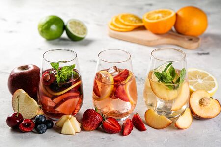 Selection of sangrias - red, pink, white and ingredients, rustic background