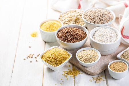 Sélection de grains entiers dans des bols blancs - riz, avoine, sarrasin, boulgour, bouillie, orge, quinoa, amarante, Banque d'images