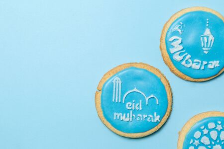 Eid Al-Adha Mubarak holiday concept - blue cookies with stenciled pictures