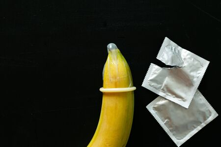 Sex education concept - letters, banana and condoms on blackboard Stockfoto