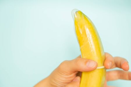 Sex education concept - hands putting condom on banana pastel background