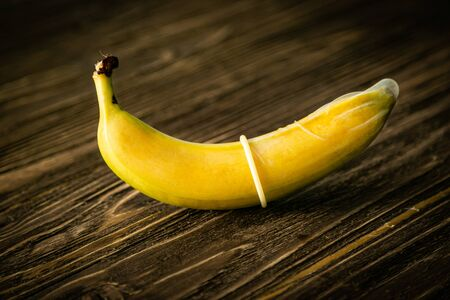Sex education concept - banana in condom on wood background