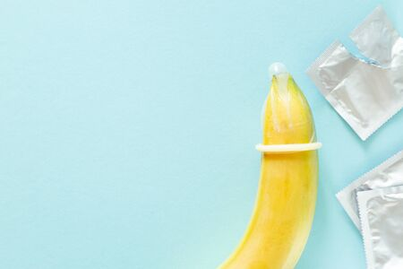 Sex education concept - banana in condom on pastel background