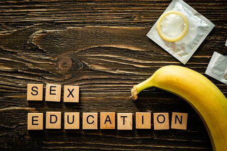 Sex education concept - letters, banana and condoms on wood background Stockfoto