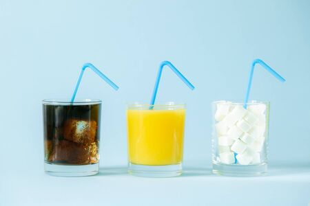 Excessive sugar consumption concept - cola, juice and sugar cubes in glasses on blue background Reklamní fotografie