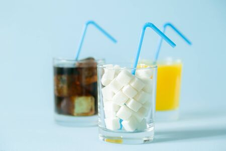 Excessive sugar consumption concept - cola, juice and sugar cubes in glasses on blue background Imagens