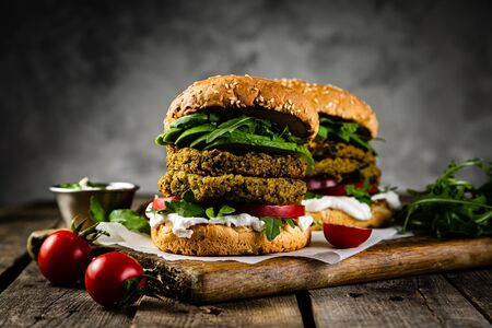 Vegan zucchini burger and ingredients on rustic wood background Banque d'images