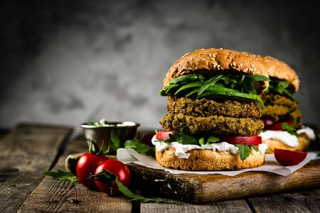 Vegan zucchini burger and ingredients on rustic wood background Stock Photo