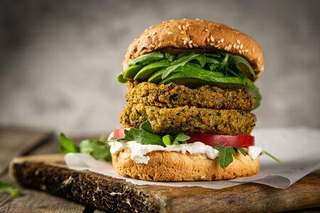 Hamburger e ingredienti vegani di zucchine su fondo di legno rustico
