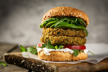 Vegan zucchini burger and ingredients on rustic wood background