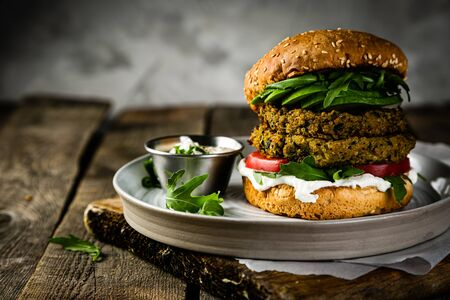 Vegan zucchini burger and ingredients on rustic wood background 版權商用圖片