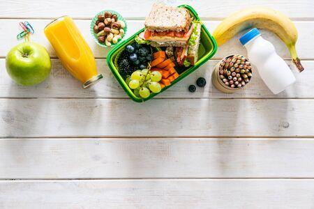 Concepto de regreso a la escuela - lonchera con jugo, manzana y plátano Foto de archivo