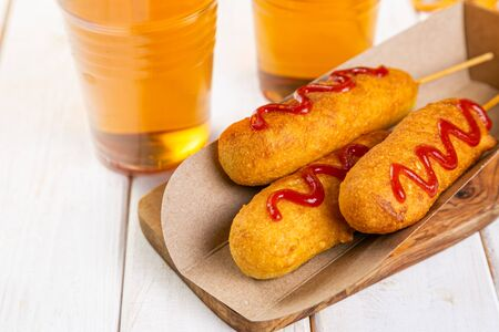 Corn dogs and beer on rustic background 스톡 콘텐츠