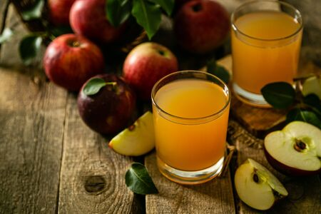 Apple juice in glass on rustic wood background Imagens
