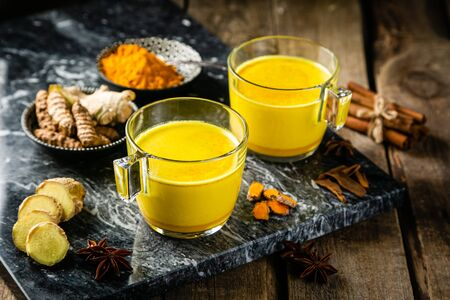 Turmeric golden milk and ingredients on wood background