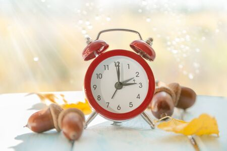 Autumn time change concept - red alarm clock on wood background