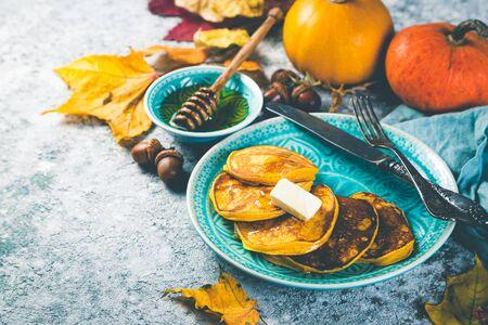 Pumpkin pancakes on rustic wood background