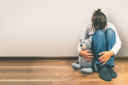 Prenatal loss concept - depressed woman holding teddy bear toy