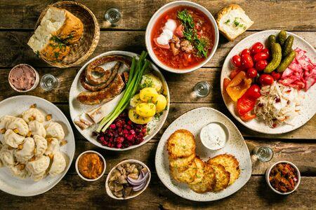 Auswahl an traditionellen ukrainischen Speisen - Borschtsch, Perogien, Kartoffelkuchen, eingelegtes Gemüse Standard-Bild