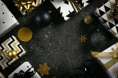 Christmas concept - black and golden presents and decorations, marble background, top view