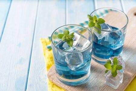 Blue lemonade in glasses on wood background