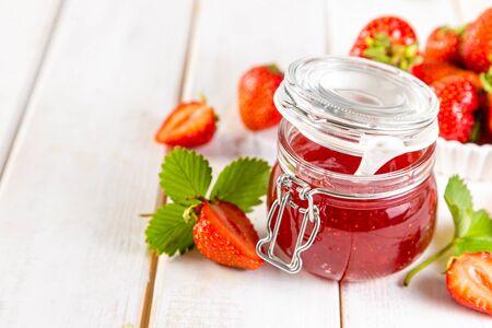 Strawberry jam in glass jar, copy space