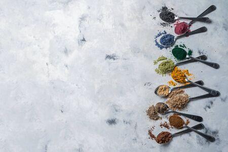 Super powders in spoons - matcha, turmeric, ginger, cocoa, spirulina, chia, cinnamon, black sesame