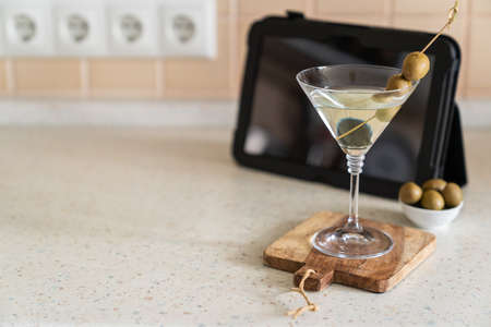 COvid-19 concept - quarantini drink martini via online communication with tablet