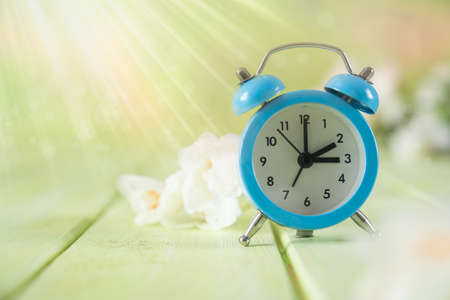 Spring time daylight saving concept - with alarm clock and flowers