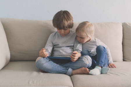 Two kids using tablet on sofa at home