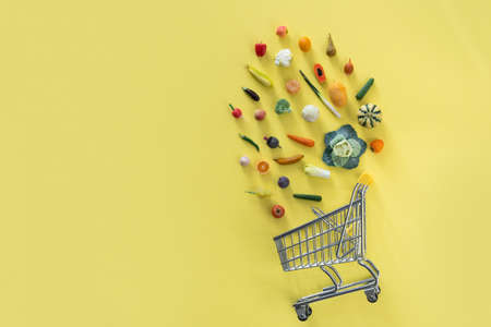 Grocery shopping concept - different foods with shopping tray on yellow background Banco de Imagens