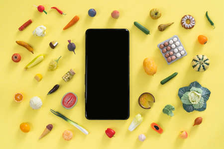 Online shopping concept - different foods and phone on yellow background Banco de Imagens
