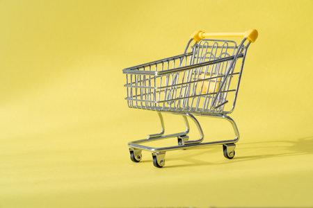 Shopping concept - shopping cart on yellow background Banco de Imagens