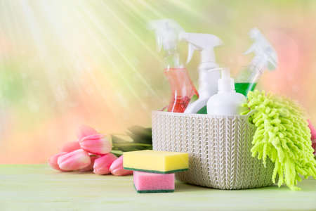 Spring cleaning concept - cleaning supplies and flowers on blur background Banco de Imagens