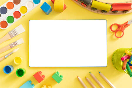 Online day care cover concept - toys and supplies with isolated tablet