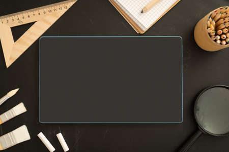 Online school class cover - celection of stationery on black board