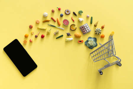 Online shopping concept - different foods and phone on yellow background Stock fotó