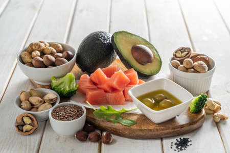 Keto diet concept - good fat sources on white wood table