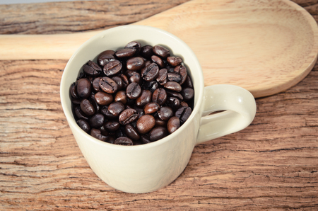 Cup full of coffee beans on wood background photo