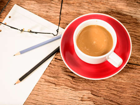Coffee Cup and office supplies on old wood table photo