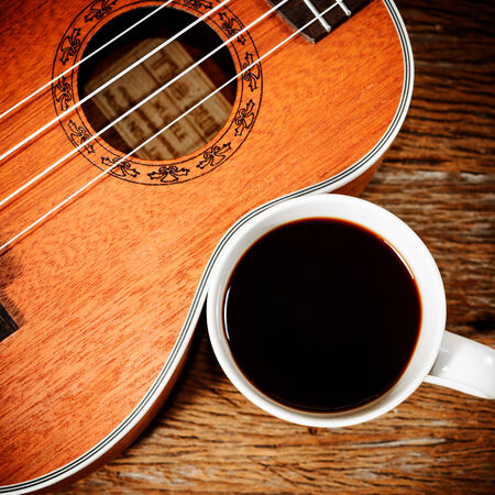 coffee cup and Ukulele on wooden table photo
