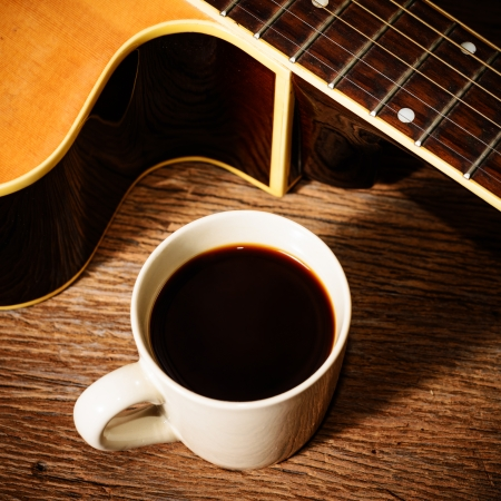 coffee cup and guitar on wooden table photo