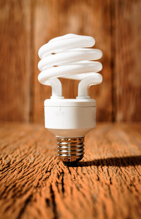 white energy saving bulb, Illuminated light bulb, CFL bulb, Realistic photo image on wood background photo
