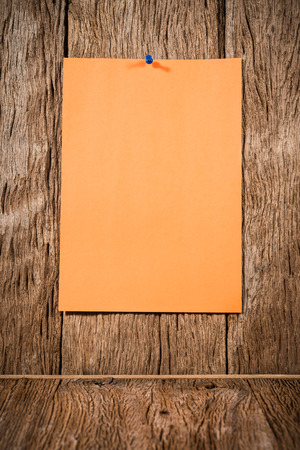instigator: orange paper with blue pin on wood background