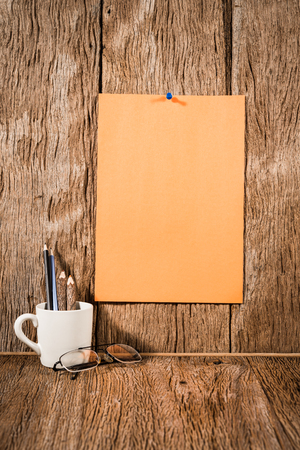 instigator: orange paper with pencil in a cup on wood background