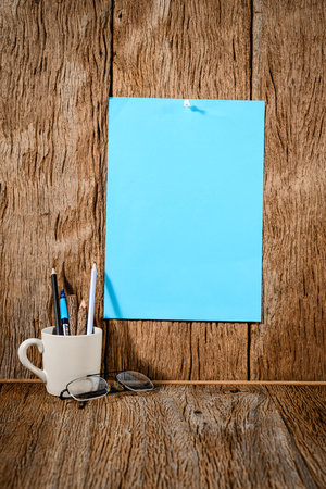 instigator: blue paper with pencil in a cup on wood background